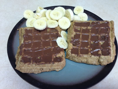Vegan Protein Waffles topped with chocolate peanut butter and banana slices